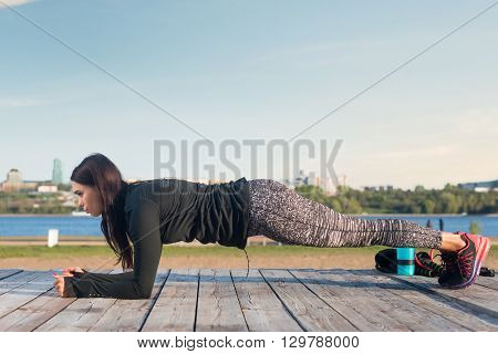 Sporty young woman doing elbow plank exercise working on abdominal muscles exercising on the river coast