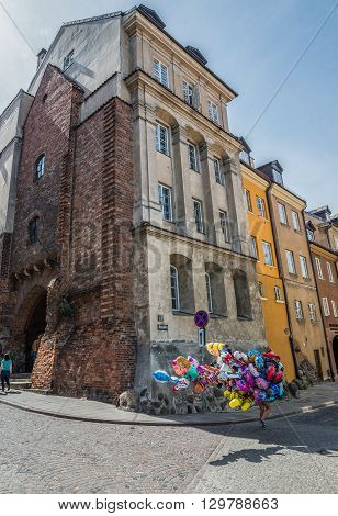 WARSAW POLAND - AUGUST 1 2015. Balloons seller walks next to tenement houses on a Brzozowa Street Old Town of Warsaw