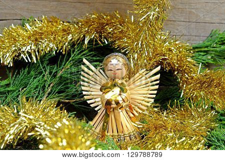 Angel made of straw with a star on his forehead for him christmas chain in gold color on old wooden table with green needles