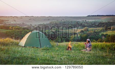 Girl near bonfire. Travel, tourism, camping - young slim sporty woman tourist brunette at the beautiful nature landscape sitting near the tent by the fire. Girl with drink in mug in her hands.