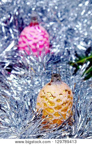 Christmas ornament in the shape of cones in pink and gold around her chain in silver color on old wooden table with green needles