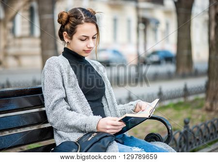 Young beautiful girl reading a book in outdoors.