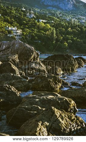 large stones in the water on the beach near the mountains wooded with houses filter