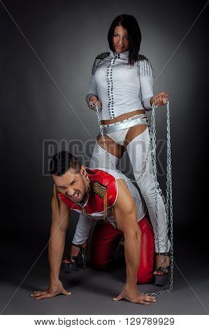 Couple of dance show. Imperious woman and guy in chains