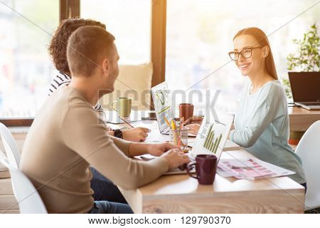 Work with pleasure. Pleasant delighted smiling woman sitting at the table and working on the laptop while cooperating with  her colleagues