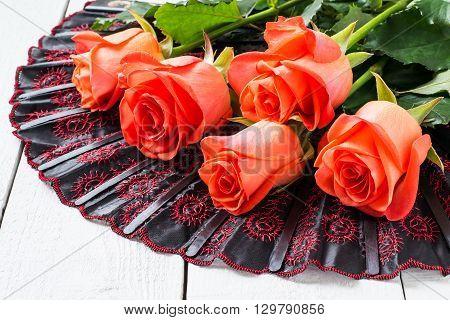 Festive bouquet of scarlet roses on a folding fan