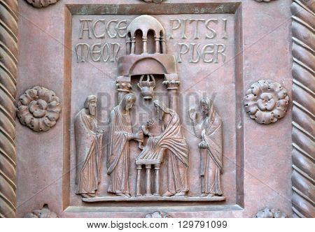 PISA, ITALY - JUNE 06, 2015: Presentation of Jesus in the Temple on the San Ranieri gate of the Cathedral St. Mary of the Assumption in Pisa, Italy on June 06, 2015