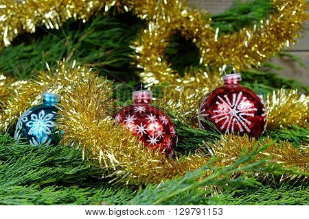 Red and one blue Christmas balls with silver stars around them christmas chain in gold color on old wooden table with green needles