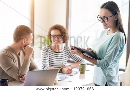 Happy working hours. Pleasant delighted smiling woman standing in the office and using tablet while her colleagues sitting at the table in the background