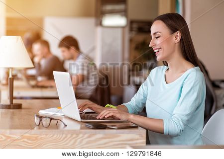 Joyful mood. Pleasant cheerful beautiful smiling woman sitting at the table and typing in the laptop while her colleagues working in the background