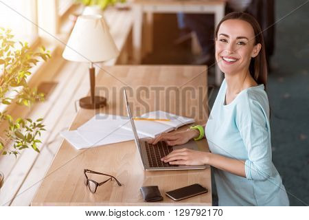 Express your emotions. Cheerful smiling beautiful woman sitting at the table and using laptop while working in the office