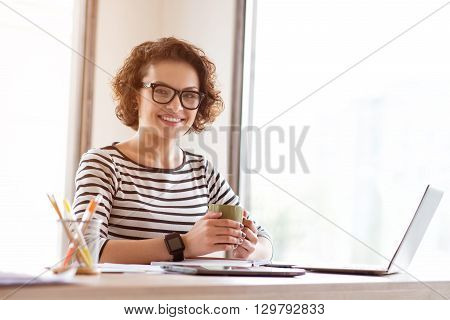 Warm up. Cheerful delighted smiling woman drinking coffee and sitting at the table while working in the office
