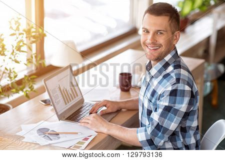 Positivity in mid. Delighted smiling handsome man sitting at the table and working on the laptop while sitting in the office
