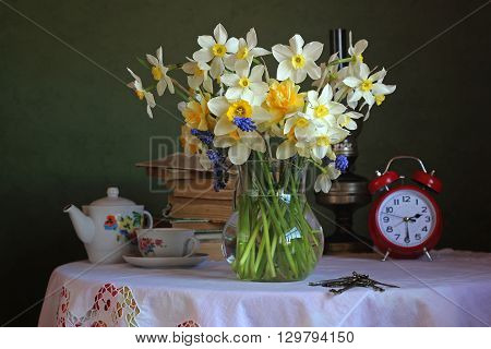 Retro still life with a bouquet of daffodils a Cup teapot books an oil lamp and alarm clock on the table with a tablecloth with lace on green background.