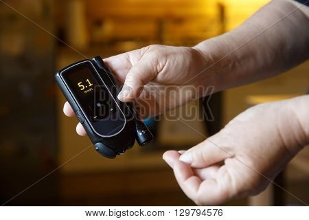 Diabetic patient testing her blood for sugar level at home; normal blood sugar level. Medical process self-diagnose common metabolic widespread and modern epidemic disease concept.