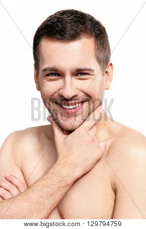 It is time for shaving. Portrait of attractive young man touching his stubble chin. He is standing with naked torso and smiling. Isolated