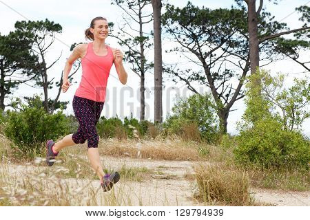 Full Length Portrait Of Woman Smiling While Running Trail Outside
