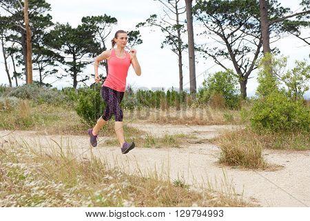 Full Length Portrait Of Woman Jogging On Trail Outside
