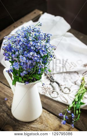 Forget-me-nots in jar on old wooden table. Still life in style rustic. Selective focus.
