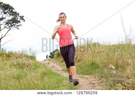 Full Length Portrait Of Sporty Woman Running On Dirt Path