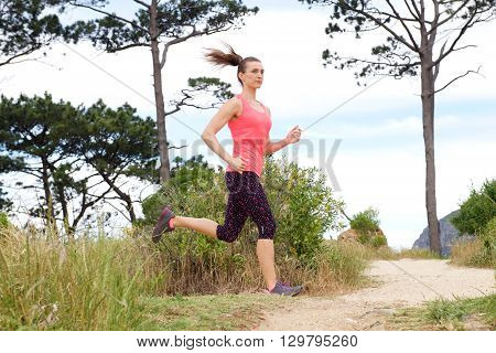 Sporty Woman Running On Dirt Path Outdoors