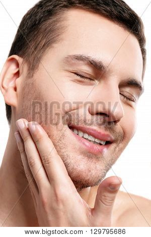Handsome young man is touching his stubble chin. He standing and smiling. His eyes are closed with enjoyment. Isolated