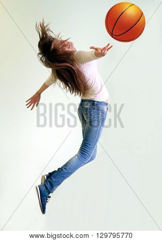 girl jumping and reaching for a basketball
