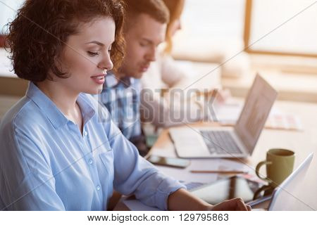 Concentrate on work. Pleasant beautiful curly woman sitting at the table and working in the office while her colleagues working in the background