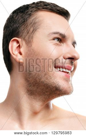 Handsome young man is standing and smiling. He is looking aside with joy. The man has bared shoulders and stubble. Isolated