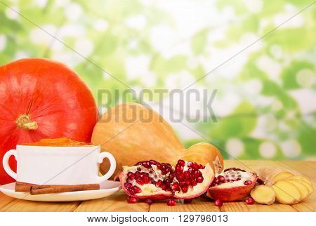 Pumpkin soup in a white cup, ginger and pomegranate on an abstract green background.