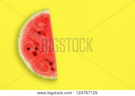 Watermelon slice on yellow table top view