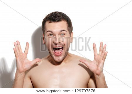Waist up portrait of naked young man looking at camera with shock. He is shouting and laughing. Man is standing and raising arms up