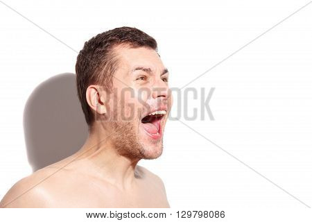 Portrait of young guy screaming with fear. He is standing with naked shoulders. Copy space in right side