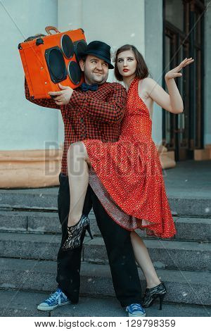 Man holding a musical installing close dancing woman retro style.