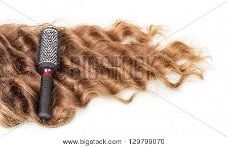 Comb and strands of curly hair isolated on white background.
