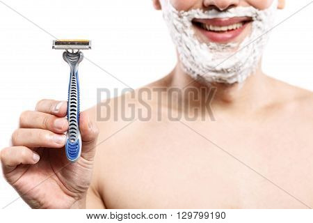 Close up of man holding a razor. He is standing and smiling. Man has shaving foam on his face. Isolated