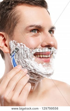 Portrait of cheerful young guy shaving with joy. He is standing and smiling. Isolated