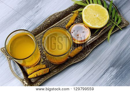 Spicy healthy Haldi or Turmeric lHoney Himalayan salt and lemon antioxidant drink with lemon on a moody background.