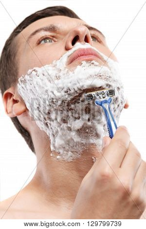 Portrait of handsome man touching razor to his chin. He is raising his head up with confidence. Man is standing with foam on face. Isolated