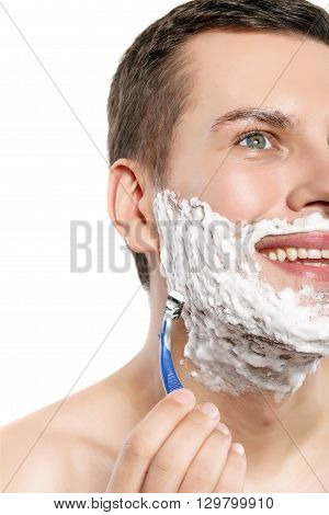 Cheerful young man is shaving his beard. He is standing and smiling. Isolated
