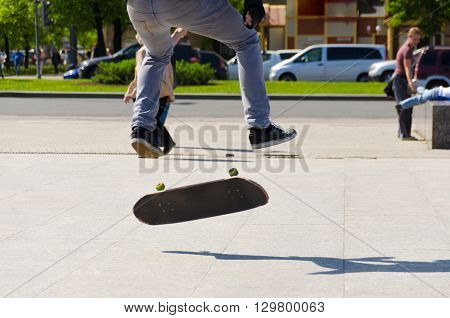 Man making skateboard trick in the street. Boy making kikcflip in sunny day. Extreme man riding by skateboard.
