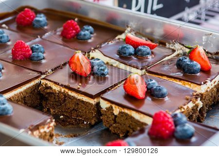 Tasty chocolate pastry with fresh berries. Street food photography on open kitchen event.