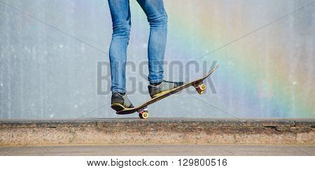 Balance on a Skateboard with raindow background. Man making skateboard trick in a city in sunny day near fontain.