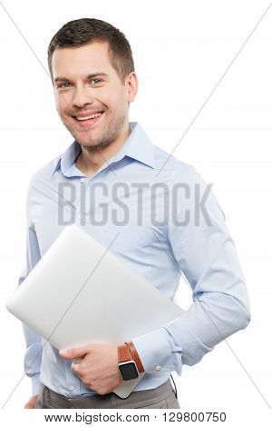 Portrait of handsome young man holding a laptop. He is standing and looking at camera with confidence. The worker is smiling. Isolated