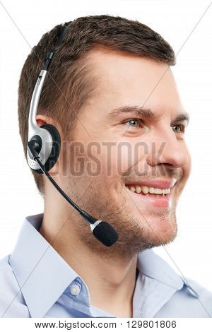 Portrait of cheerful male operator standing with headset. He is smiling and looking forward with joy. Isolated