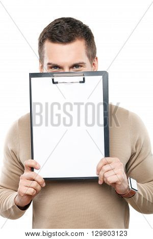 Portrait of attractive young guy holding a folder of papers. He is standing and peeping though it with joy. Isolated