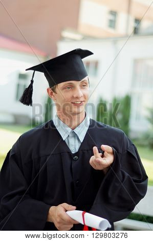 The graduate of the University of something said. He is dressed in a black cloak and a hat. Student holding his diploma.