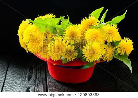 Original festive bouquet of dandelions in a red hat on a dark wooden table