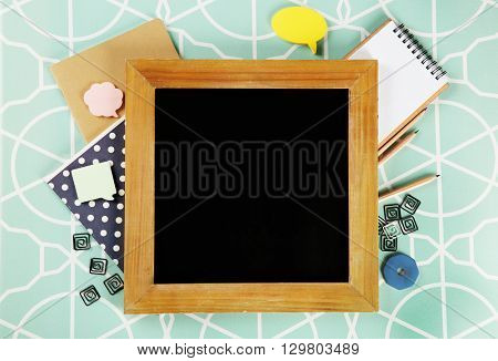 Small school blackboard with stationery on patterned background