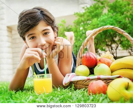 Portrait of a happy teen boy lying down on fresh green grass field and drinking tasty juice, eating fruits, enjoying healthy nutrition in the summer camp